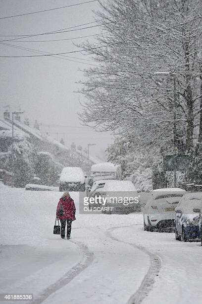 A woman walks along a snowcovered road in the village of Marsden northern England on January 21 during heavy snowfall A Met Office warning of snow is...