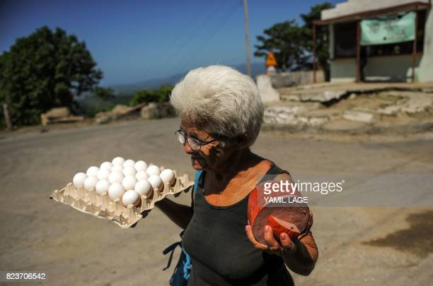 A woman walks along a street after buying eggs at a grocery store in San Luis Santiago de Cuba province on June 20 2017 Each Cuban home receives...
