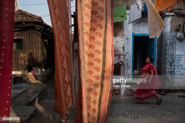 A woman walks along a street as colourful sarees dry in the foreground in the northern part of Kolkata which is known as a more historic quarter The...