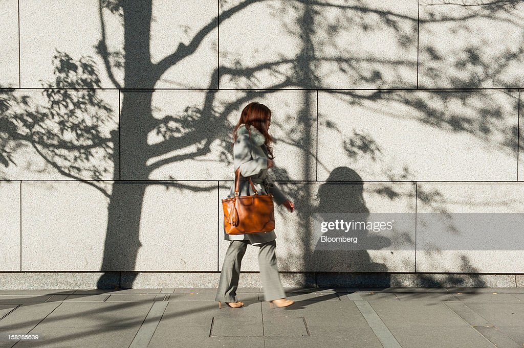A woman walks along a street during the morning commute in Tokyo, Japan, on Monday, Dec. 10, 2012. Japan's economy shrank in the last two quarters, meeting the textbook definition of a recession, as the dispute with China, the country's biggest export market, caused consumers there to shun Japanese products and contributed to Japan's worst year for exports since the global recession in 2009. Photographer: Noriko Hayashi/Bloomberg via Getty Images