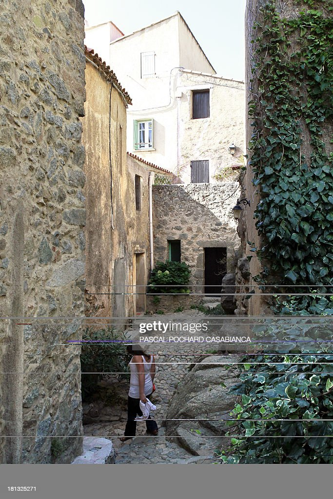 A woman walks along an alley on September 19, 2013 in San Antonino village, on the French Mediterranean island of Corsica. San Antonino is listed as one of the most beautiful villages of France.