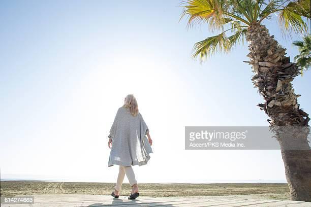 Woman walks along boardwalk towards empty beach