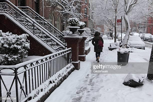 Woman walks along Brooklyn Heights street in winter snow storm
