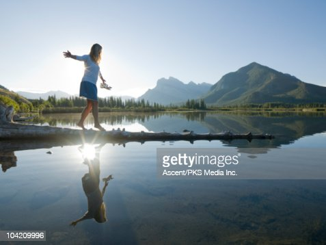 Woman walks along submerged log in mountain lake : Stock Photo