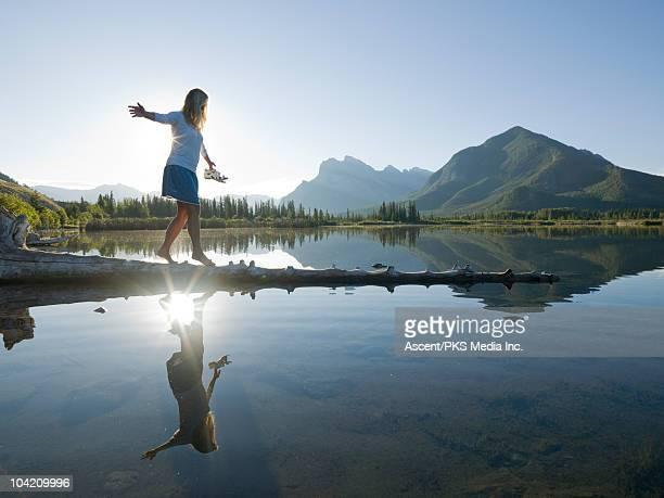 Woman walks along submerged log in mountain lake