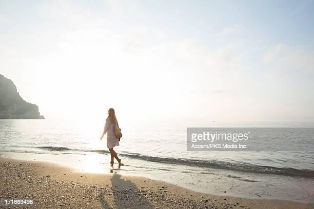 Woman walks along surf edge, at sunrise
