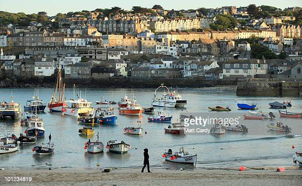 A woman walks along the beach as the evening sun reflects on streets of houses in St Ives on May 27 2010 in Cornwall England A recent report has...