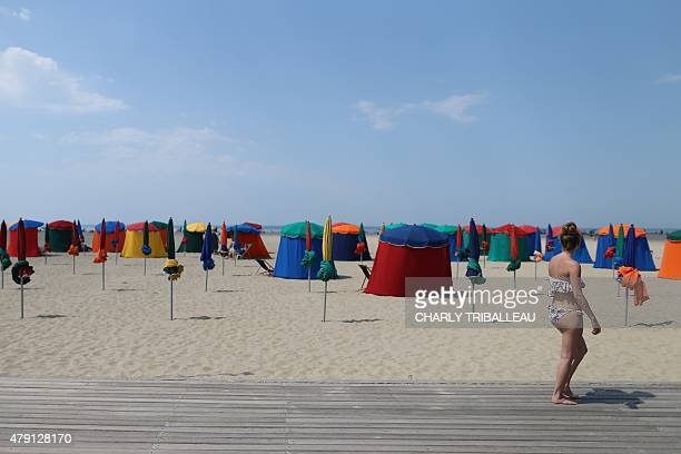 A woman walks along the beach in the French northwestern city of Deauville on July 1 as a blistering heatwave sweeps through Europe with temperatures...