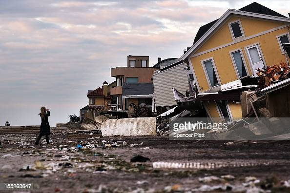 A woman walks along the beach in the heavily damaged Rockaway neighborhood in Queens where a large section of the iconic boardwalk was washed away on...