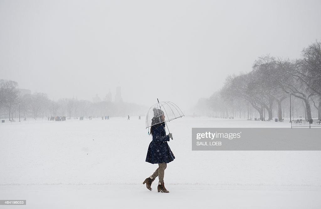 A woman walks along the National Mall in Washington, DC, January 21, 2014, as snow falls during a storm. The northeastern United States hunkered down Tuesday for a major snowstorm that forecasters warned could leave as much as one foot (30 centimeters) of snow in some places. Downtown Washington fell virtually silent after the federal government, seeing the swift-moving cold front approaching, closed its doors and told civil servants to stay home. Many offices and schools followed suit, as 20 mile (32 kilometer) per hour winds whipped the falling snow through the unusually quiet streets. Enough snow was expected to fall on the US capital to turn the evening rush hour into a Beltway traffic nightmare, as the storm churned its way into New York and the northeastern New England states. AFP PHOTO / Saul LOEB