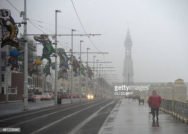 A woman walks along the promenade through rain and strong winds in Blackpool northern England on January 9 2015 Engineers have been working to...