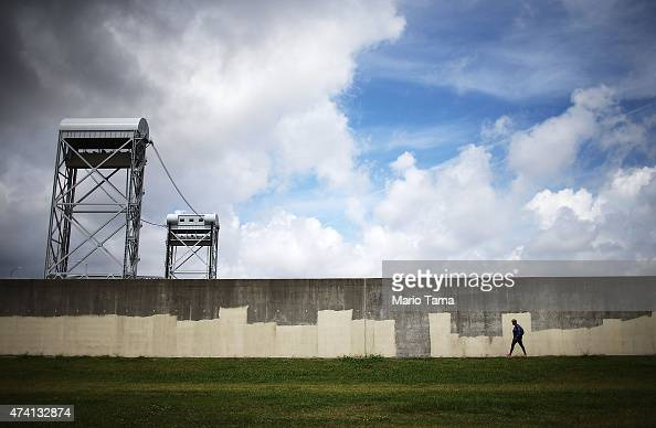A woman walks along the rebuilt Industrial Canal levee wall in the Lower Ninth Ward on May 18 2015 in New Orleans Louisiana The levee was destroyed...