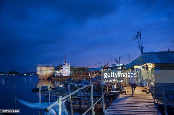 A woman walks along the rickety bridges above the seawater that connect the houses on stilts together behind her is a ship yard where many pirates...