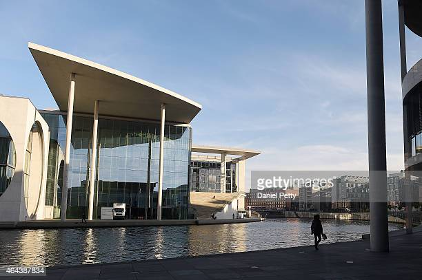 A woman walks along the Spree River across from the MarieElisabethLüdersHaus on November 17 2014 in Berlin Germany