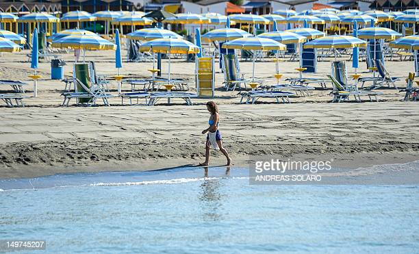 Woman walks along the waters edge at a closed private beach in Lido di Ostia near Rome on August 3 2012 during a strike action entitled ' We close...