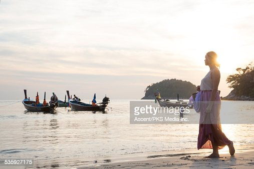 Woman walks along white sand beach, looks to boats : Stock Photo