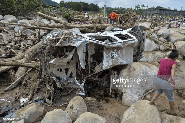 TOPSHOT A woman walks amidst the rubble left by mudslides following heavy rains in Mocoa Putumayo department southern Colombia on April 2 2017 The...