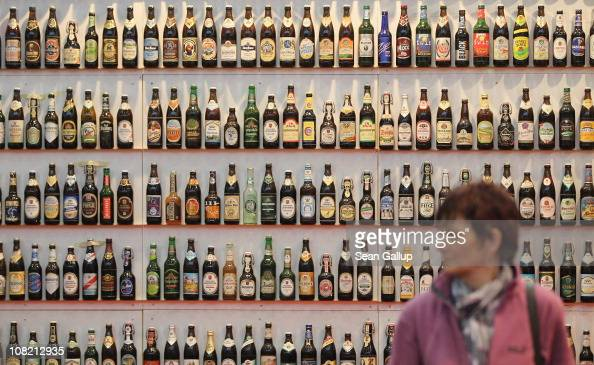 A woman walks among hundreds of bottles of German beer meant to represent the approximately 5000 brands of German beer at a stand at the 2011 Gruene...