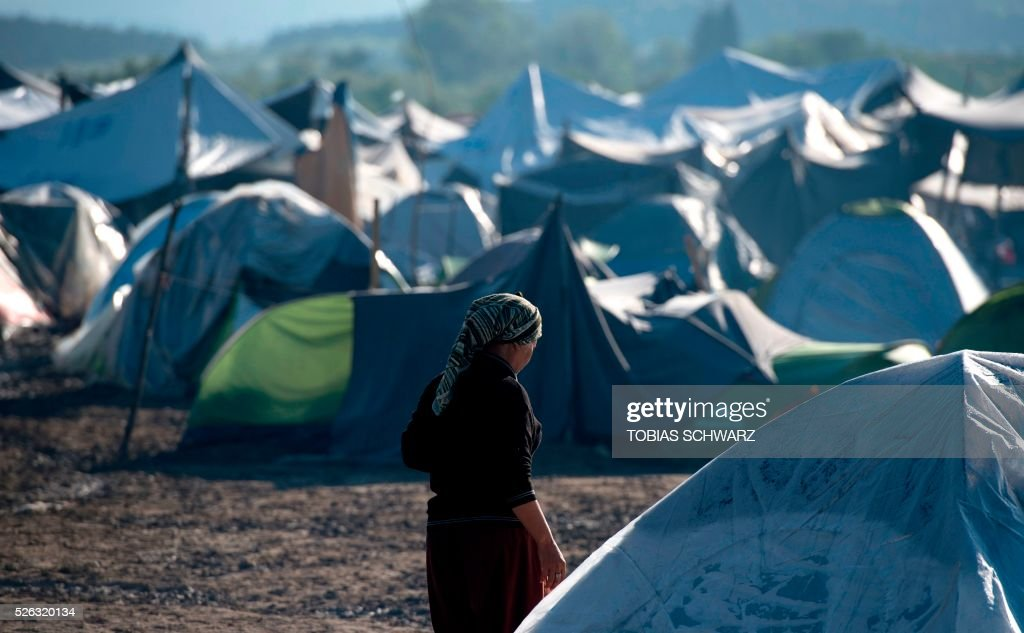 A woman walks among tents at a makeshift camp for migrants and refugees near the village of Idomeni, not far from the Greek-Macedonian border, on April 30, 2016. Some 54,000 people, many of them fleeing the war in Syria, have been stranded on Greek territory since the closure of the migrant route through the Balkans in February. / AFP / TOBIAS