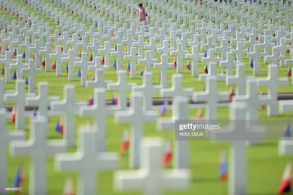 A woman walks amongst the graves of soldiers who fell during World War II, searching for a grave of a relative during a service to mark US Memorial Day at the Manila American Cemetery in Fort Bonifacio in Manila on May 26, 2013. At least 17,000 graves are in the park that pays tribute to US and Philippines soldiers that fought side-by-side during World War II. The US marks Memorial Day on May 27.