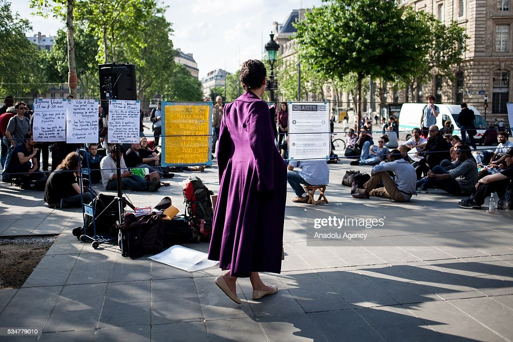 A woman walks around Place the Republique and read some banners during the Global Debout meeting 'Nuit Debout' ('The Night awake' or Up all night') in Paris, France on May 27, 2016.