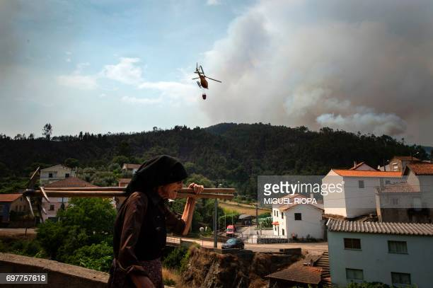 A woman walks as a firefighter helicopter flies over the village of Carvalho next to Pampilhosa da Serra on June 19 2017 More than 1000 firefighters...