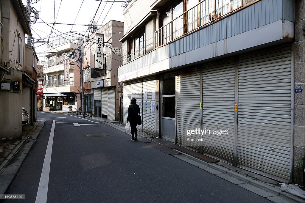 A woman walks at a almost shuttered shopping street near Shinjuku area on February 7, 2013 in Tokyo, Japan. A recent servey shows Tokyo as the most expensive city in the world and Osaka ranked second.