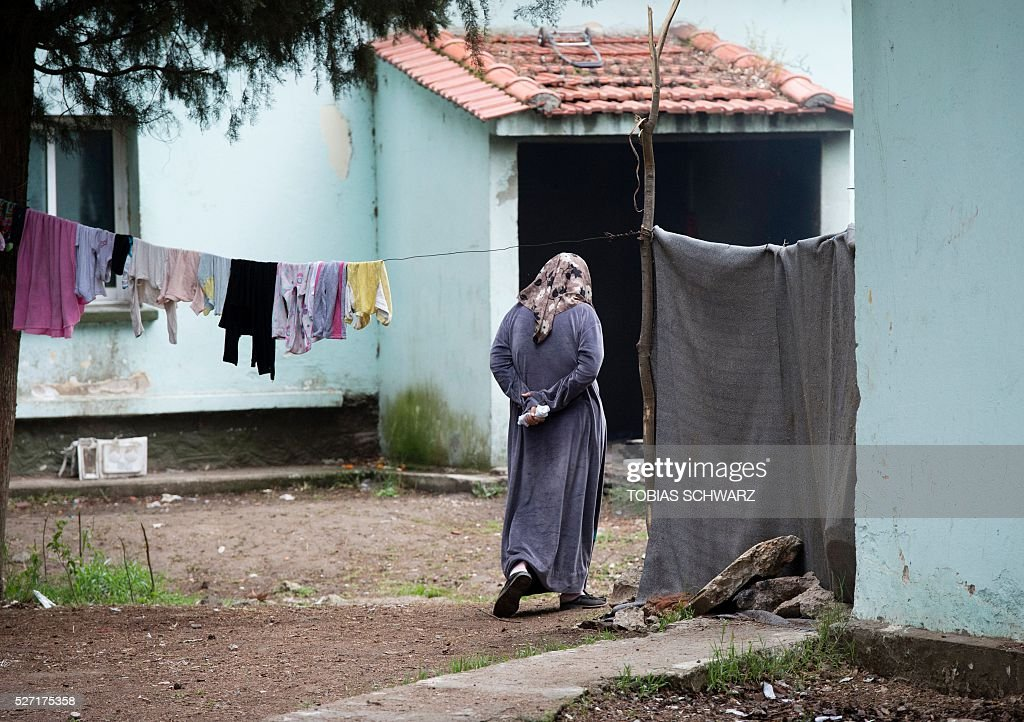 A woman walks at a makeshift camp for migrants and refugees at the Greek-Macedonian border near the village of Idomeni on May 2, 2016. Some 54,000 people, many of them fleeing the war in Syria, have been stranded on Greek territory since the closure of the migrant route through the Balkans in February. / AFP / TOBIAS