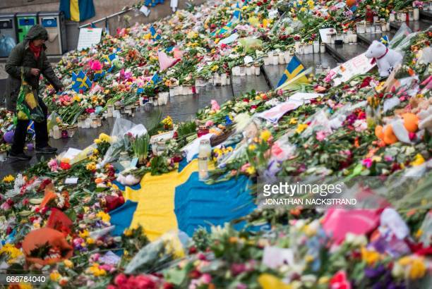 A woman walks at a makeshift memorial to commemorate the victims of Friday's terror attack near the site where a truck drove into Ahlens department...