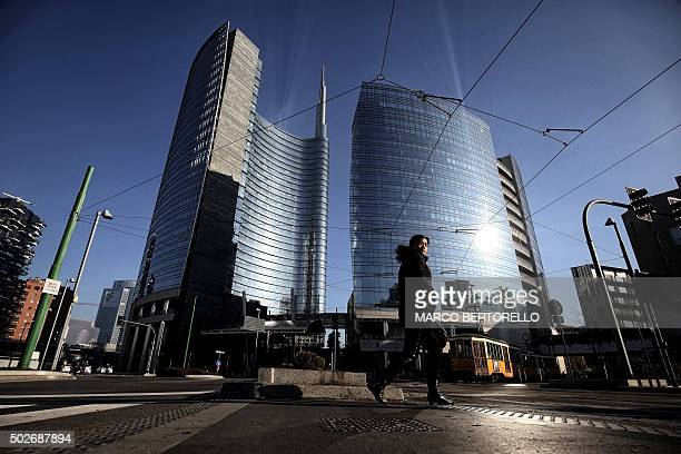 A woman walks at piazza Gae Aulenti in Milan on December 28 2015 Drivers in Milan will face a limit on daytime travel three days as the northern...