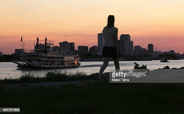 A woman walks atop an earthen levee on the Mississippi River in the Lower Ninth Ward as the Steamboat Natchez passes on August 26 2015 in New Orleans...