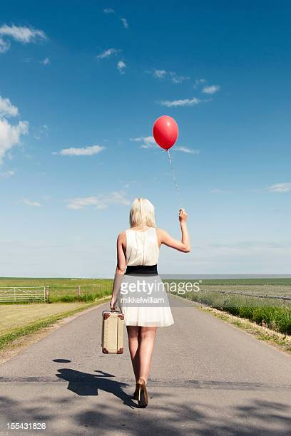 Woman walks away while holding balloon and suitcase