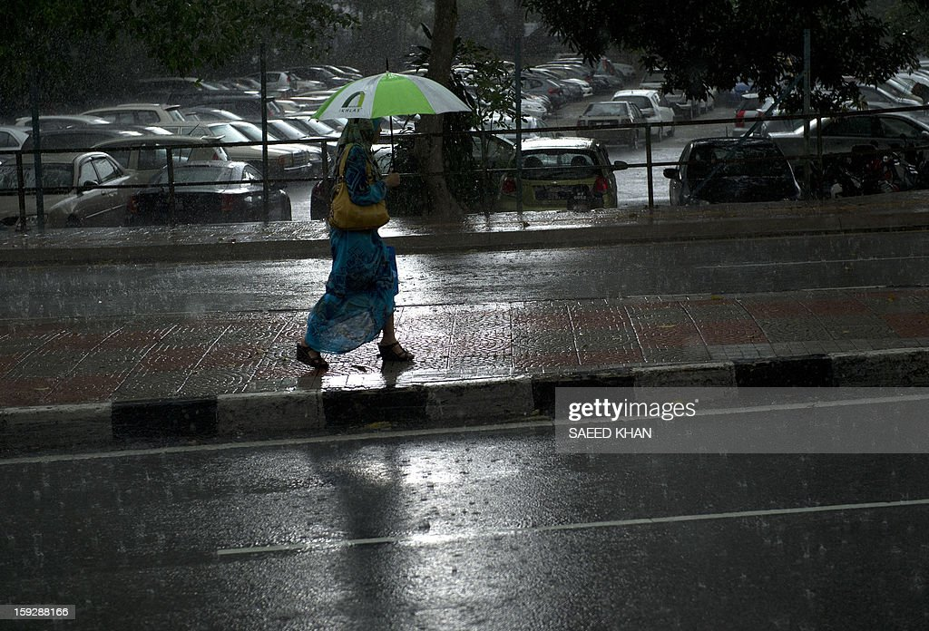 A woman walks back from the office during heavy rain in the business hub of Kuala Lumpur on January 11, 2013. AFP PHOTO / Saeed Khan