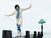 Woman Walks, Balancing With Her Arms Out on a Breakwater