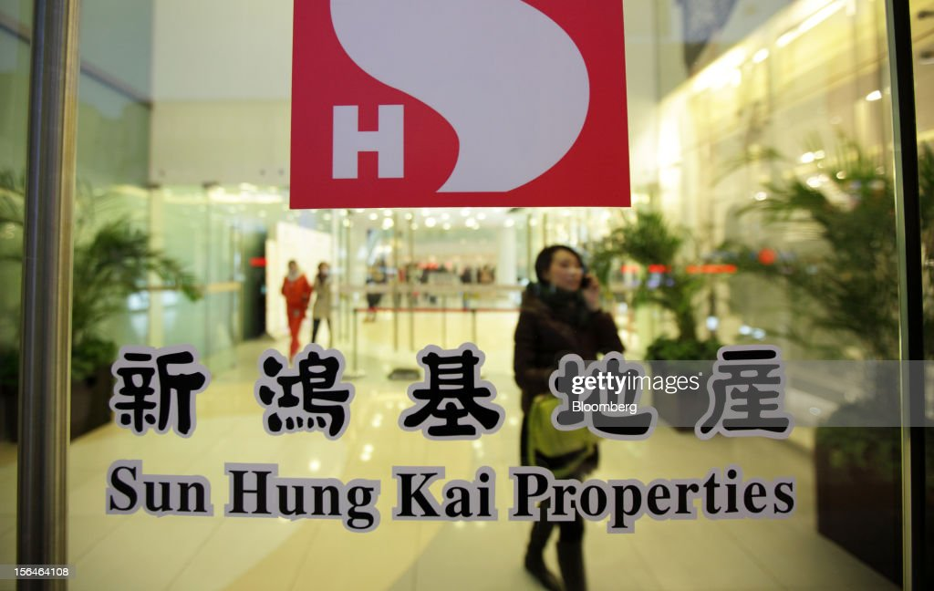 A woman walks behind the Sun Hung Kai Properties Ltd. logo at a commercial building owned by the company in Beijing, China, on Sunday, Nov. 11, 2012. Sun Hung Kai will continue buying land in Hong Kong, co-chairman Thomas Kwok said yesterday. Photographer: Tomohiro Ohsumi/Bloomberg via Getty Images