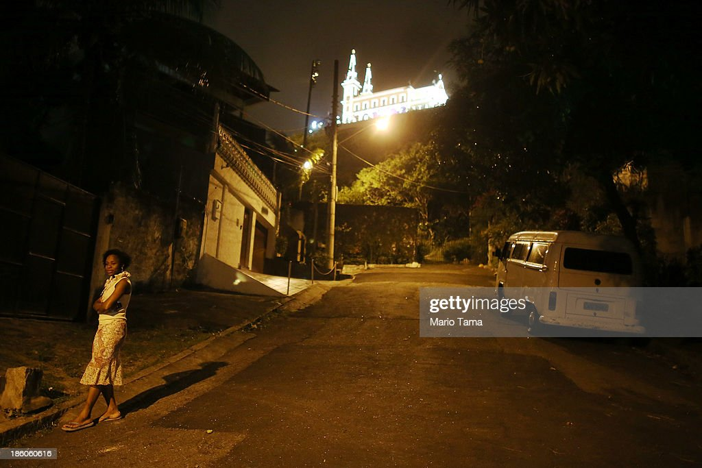 A woman walks below the Nossa Senhora da Penha Church on the final day of the annual October feast of the patron saint marking the 378th anniversary of the church on October 27, 2013 in Rio de Janeiro, Brazil. Pilgrims often climb the entire 382 steps that lead to the church, originally constructed in 1635, which is perched on a rocky hill. Brazil holds more Catholics than any other country.