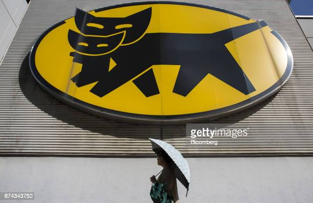 A woman walks beneath signage for Yamato Holdings Co outside one of the company's facilities in Tokyo Japan on Friday April 28 2017 Yamato's shares...