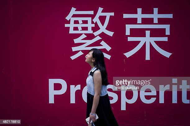 A woman walks beside a board with the characters for 'prosperity' in Chinese in Beijing on July 28 2015 Chinese shares sank on July 28 a day after...