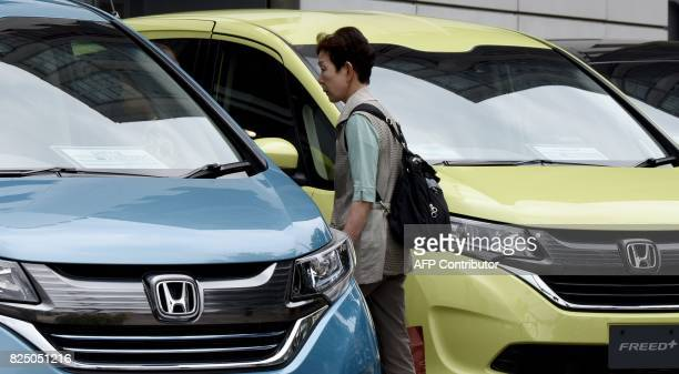 A Woman Walks Beside Vehicles From Honda Motor Displayed In Front Of Their Headquarters Tokyo