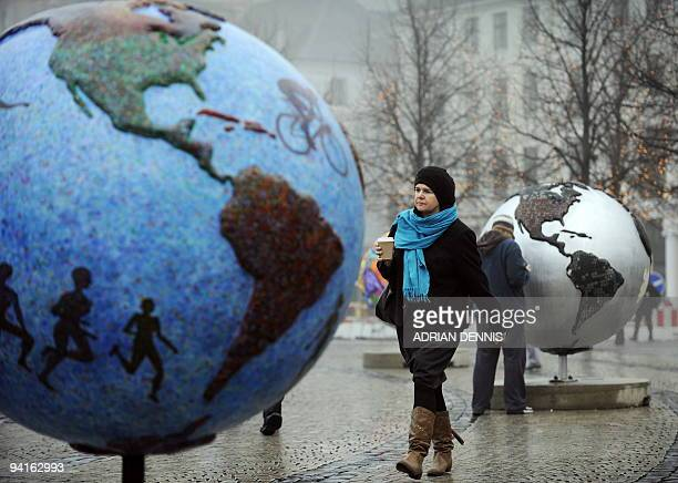 A woman walks between displays entitled 'Cool Globes' an exhibition about combating global warming and climate change in the Kongens Nytorv area in...