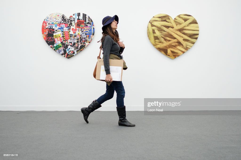 A woman walks between 'I Love Protests' (L) and 'I Love Fries' by Rob Pruitt at the Frieze Art Fair on October 6, 2017 in London, England. The annual event sees galleries showcase work by thousands of artists from around the world. The Frieze Art Fair runs from 5-8 October, 2017.