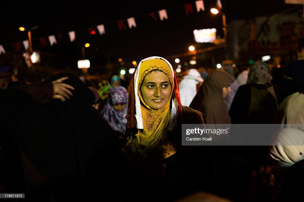 A woman walks betwen supporters of ousted president Mohamed Morsi after breaking the daily Ramadan fast on the second day of Ramadan, the sacred holy month for Muslims where many will fast from sun-up to sun-down on July 11, 2013 in Cairo, Egypt. Egypt continues to be in a state of political paralysis following the ousting of former President and Muslim Brotherhood leader Mohamed Morsi by the military. Adly Mansour, chief justice of the Supreme Constitutional Court, was sworn in as the interim head of state in a ceremony in Cairo on the morning of July 4.
