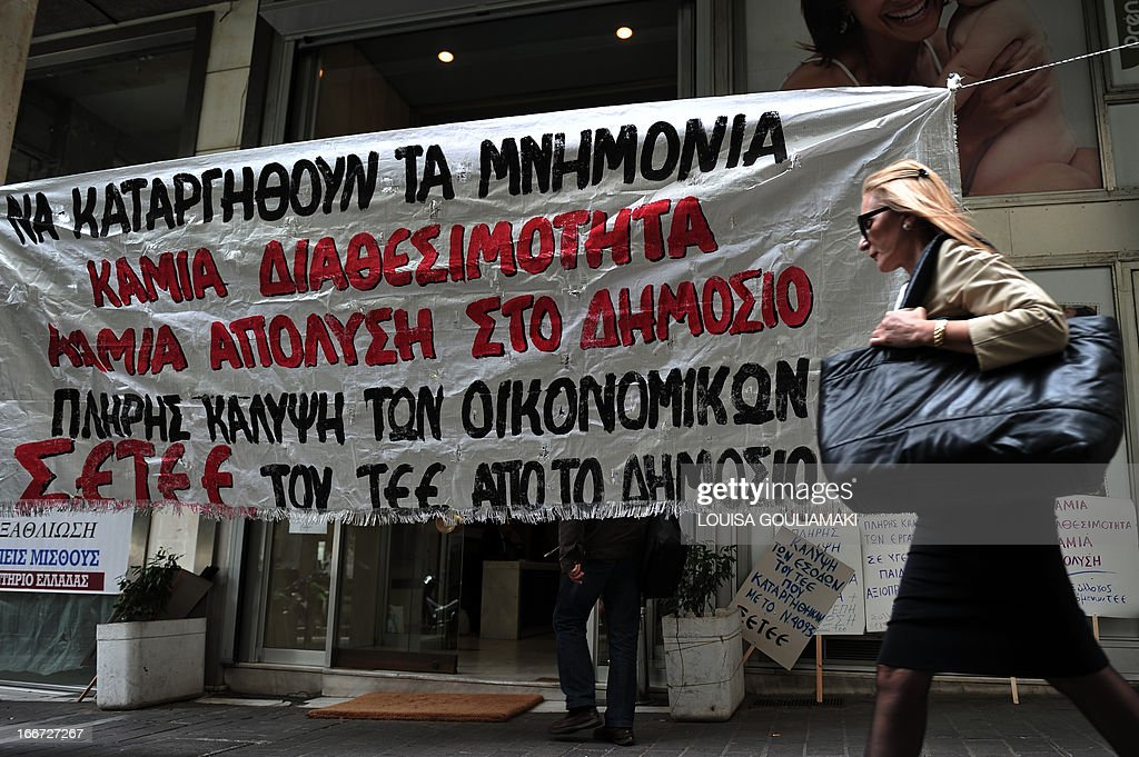 A woman walks by a banner set outside Greece's technical chamber bearing slogans against layoffs in public sector on April 16 2013 in Athens a day...