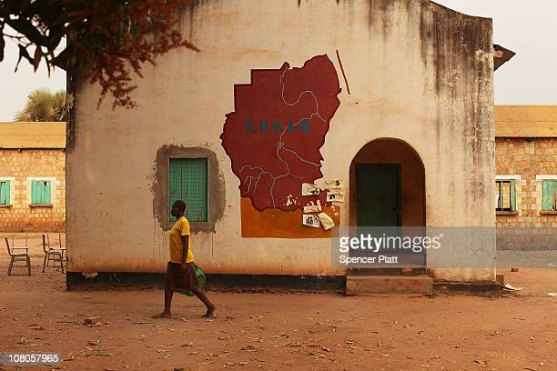 A woman walks by a building with a map of Sudan painted on it at the close of polls following a week of voting in the independence referendum January...