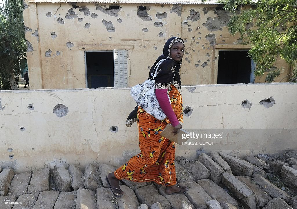A woman walks by a bullet riddled police station one day after Islamist gunmen battled French and Malian troops, on February 11, 2013 in Gao.