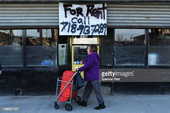 A woman walks by a closed business near the beach in Rockaway on December 13 2012 in New York City Much of the Rockaway neighborhood is still...