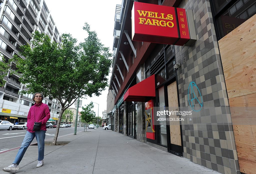 A woman walks by a damaged Wells Fargo branch in downtown Oakland California on May 02 2015 Hundreds marched throughout the city on May 1 to mark...
