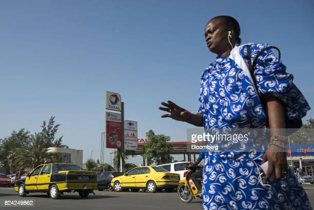 A woman walks by a gas station operated by Total SA in Dakar Senegal on Friday July 28 2017 Senegalese voters will elect a new parliament on Sunday...