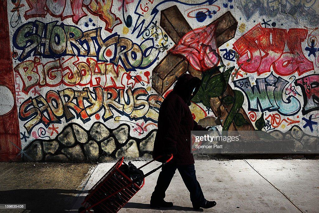 A woman walks by a graffiti memorial on a wall in memory of an individual killed in the Bedford-Stuyvesant neighborhood on January 17, 2013 in the Brooklyn borough of New York City. Visual memorials honoring residents who in many cases met violent ends decorate many Brooklyn neighborhoods. New York Governor Andrew Cuomo recently signed into law the New York Secure Ammunition and Firearms Enforcement Act, one of the toughest gun laws in the country.