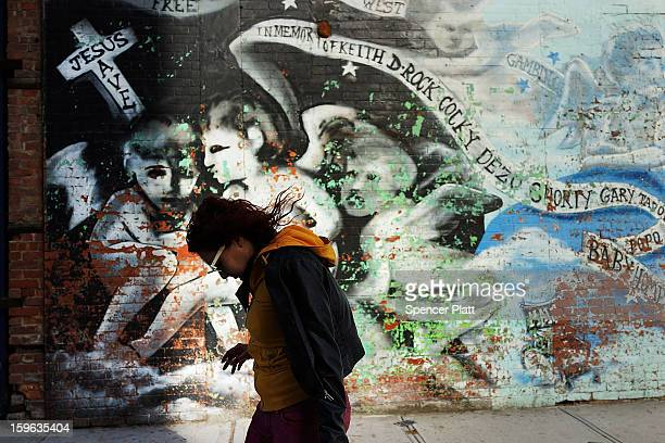 A woman walks by a graffiti memorial on a wall in memory of individuals killed in the BedfordStuyvesant neighborhood on January 17 2013 in the...